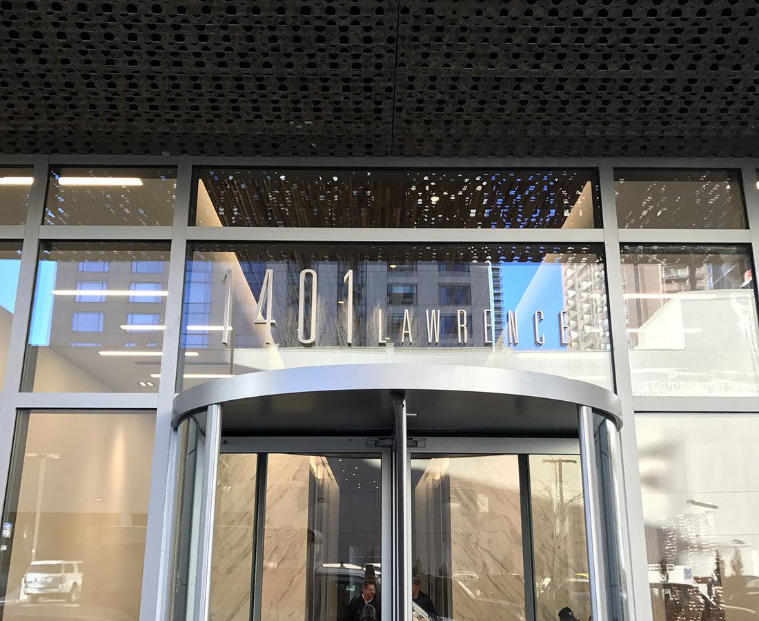 1401 Lawrence address entrance signage above revolving door.