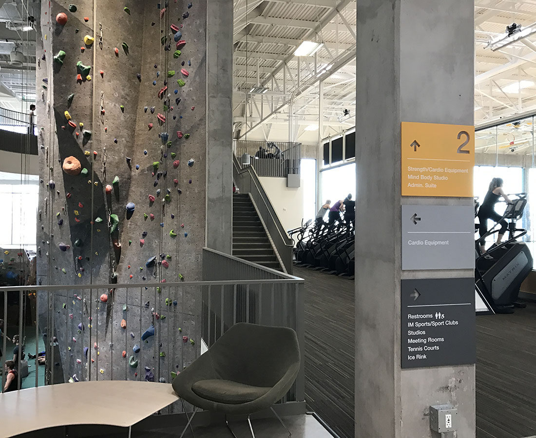 CU Boulder Rec Center climbing wall direction signs stacked