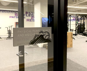Gray ADA sign for fitness center at the Colorado Rockies Clubhouse at Coors Field