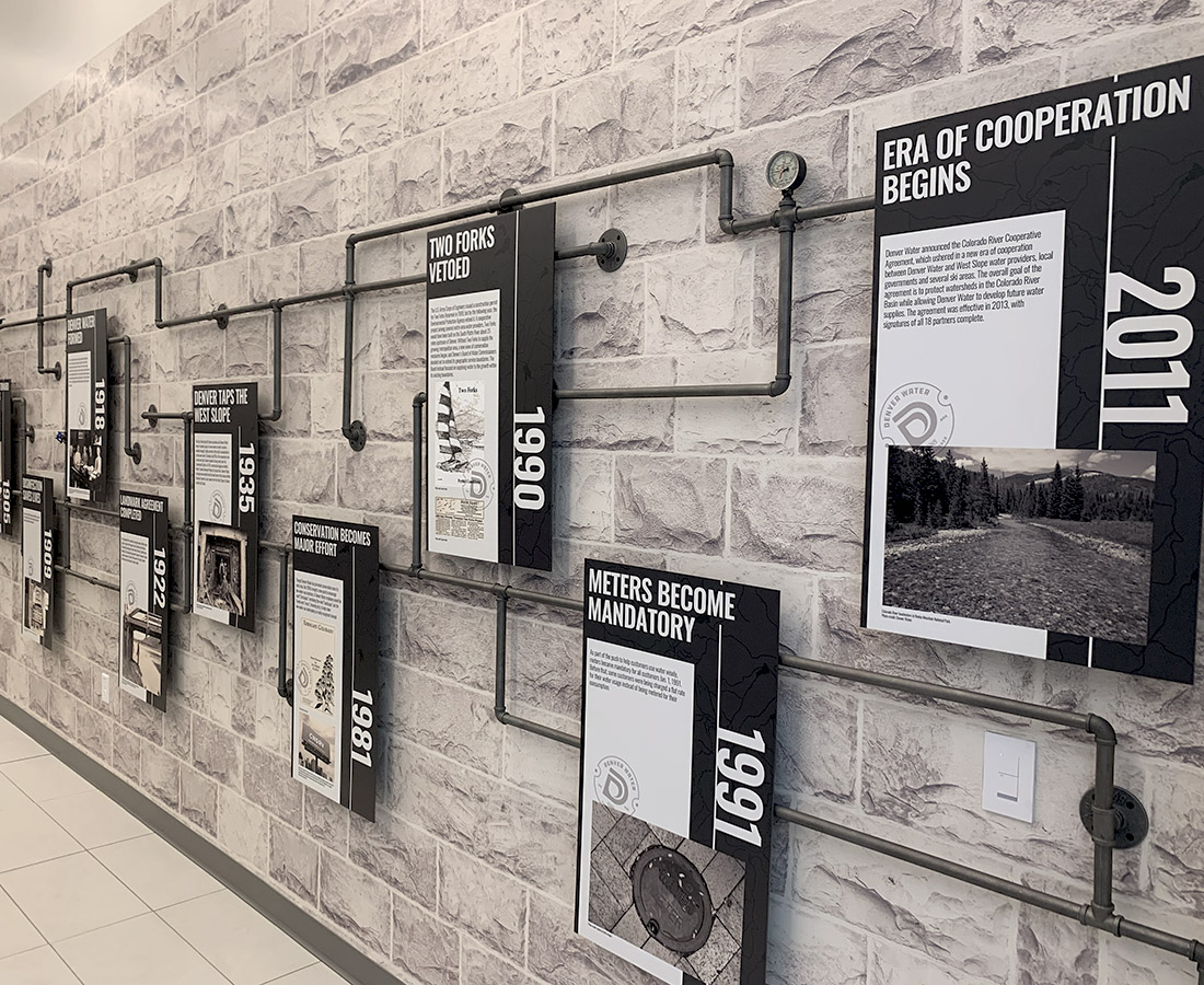 Custom history timeline with vintage water pipes and informational panels at Denver Water