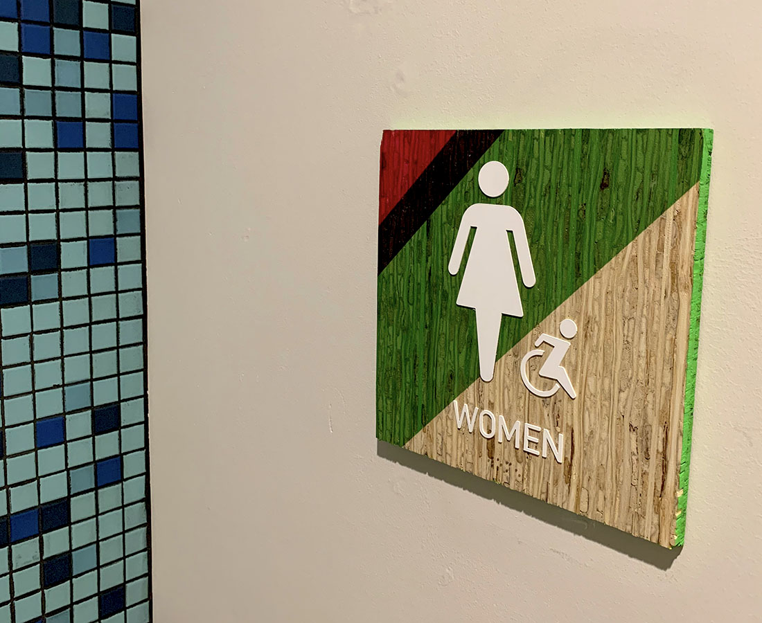 Colab Apartments interior restroom sign pink, blue and green kirei board