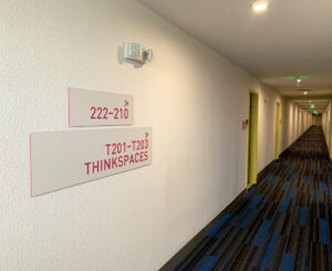 Colab Apartments interior wayfinding hallway signage pink