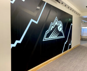 Illuminated steel Rockies logo graphic wall at the Colorado Rockies Clubhouse at Coors Field