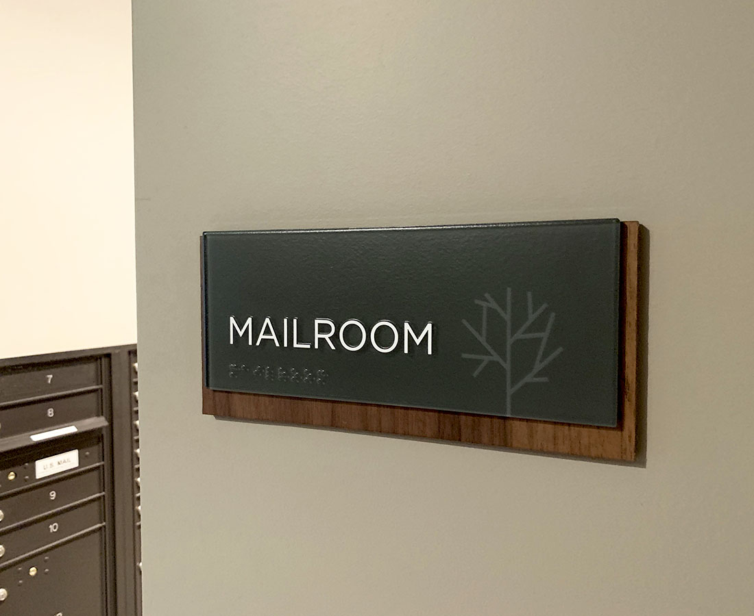 Sova on Grant interior mailroom sign made of glass and wood