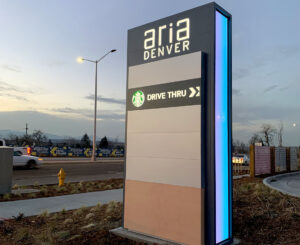 Aria Denver illuminated color changing monument sign, Starbucks tenant panel