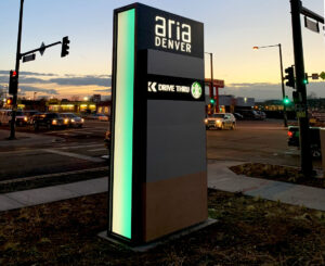 Aria Denver illuminated color changing monument sign, Starbucks tenant panel