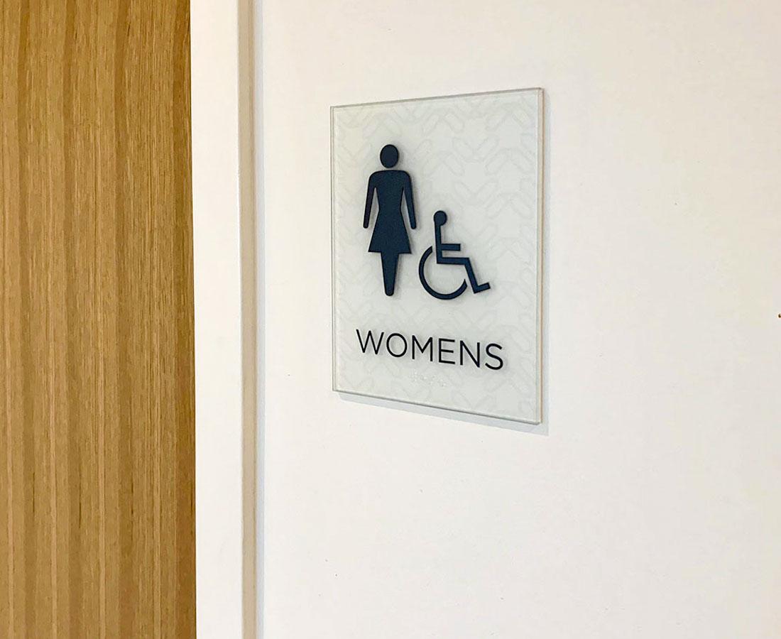 Interior glass restroom sign at Roth Living showroom in Denver