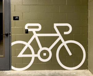 Interior green vinyl wall bike graphic and ADA compliant room ID sign at Modera LoHi