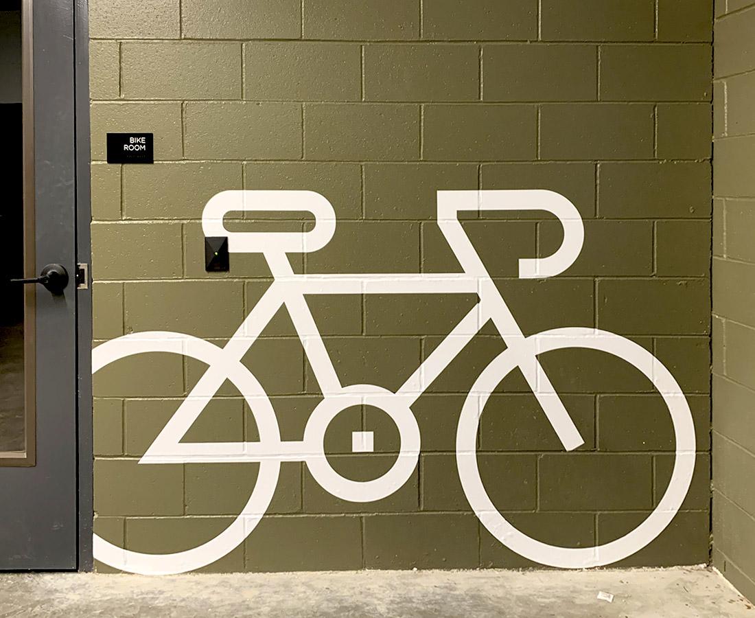 Interior green vinyl wall bike graphic and ADA compliant room ID sign at Modera LoHi